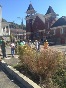 The group checks out the rain garden in a municipal parking lot in Millvale.